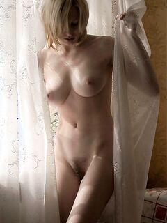 Оголенная блондинка красуется собой у окна