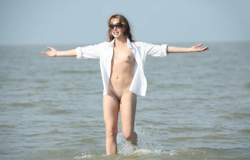 Оголенная милашка плескается в море