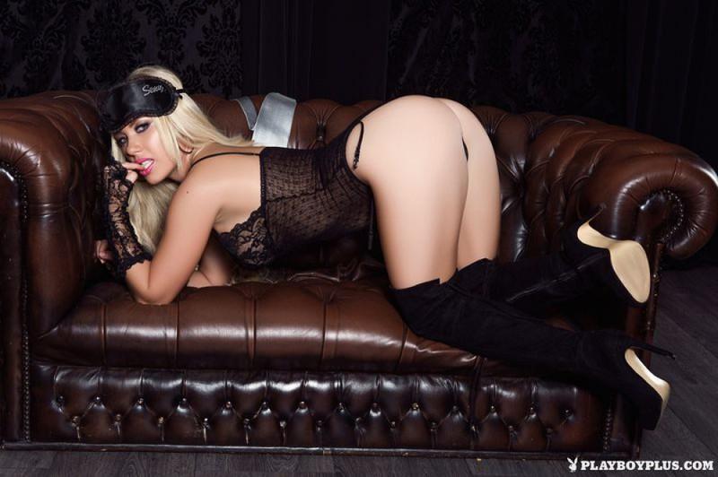 Голая блондинка позирует на кожаном диване