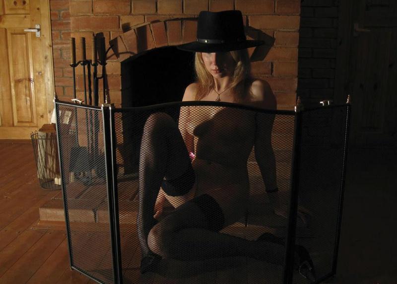 Дама в шляпе раздевается у камина