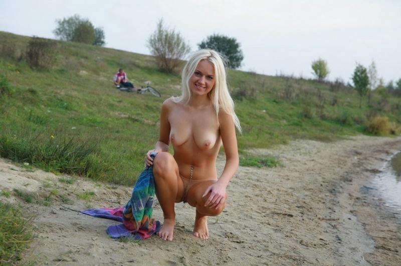 Шикарная блондинка нагишом прогуливается возле озера