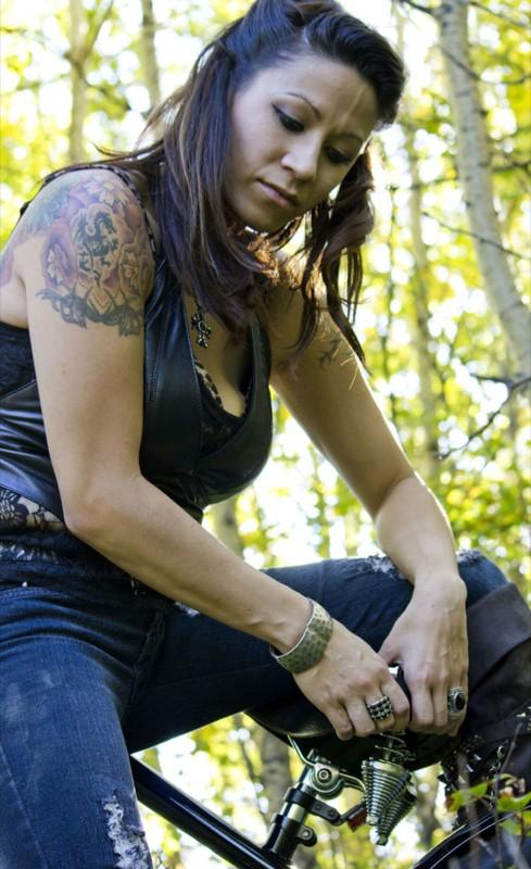 Жгучая брюнетка сидит в лесу без одежды
