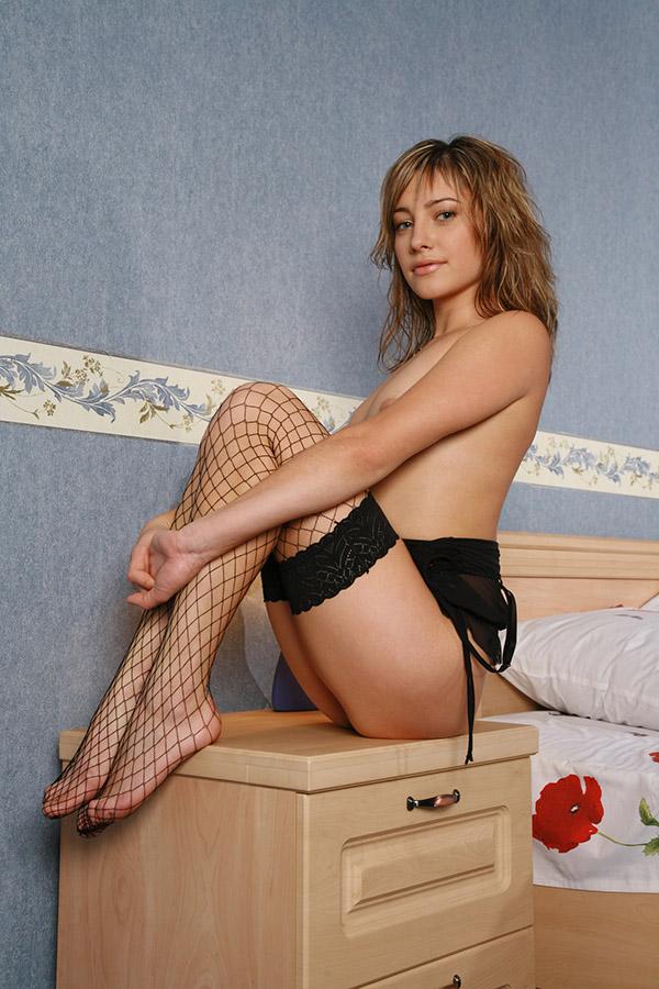 Стройная мамзель обнажается в спальне