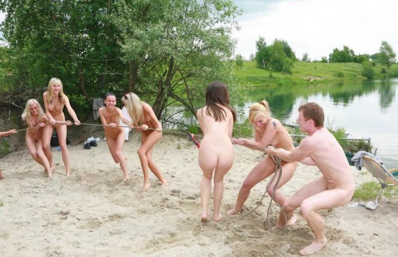 Молодые нудисты отдыхают на водоеме