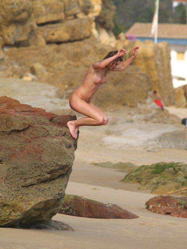 Голая блондинка играется на пляже в песке