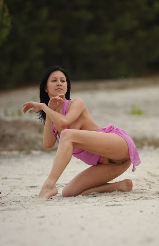 Обнаженная балерина танцует на пляже