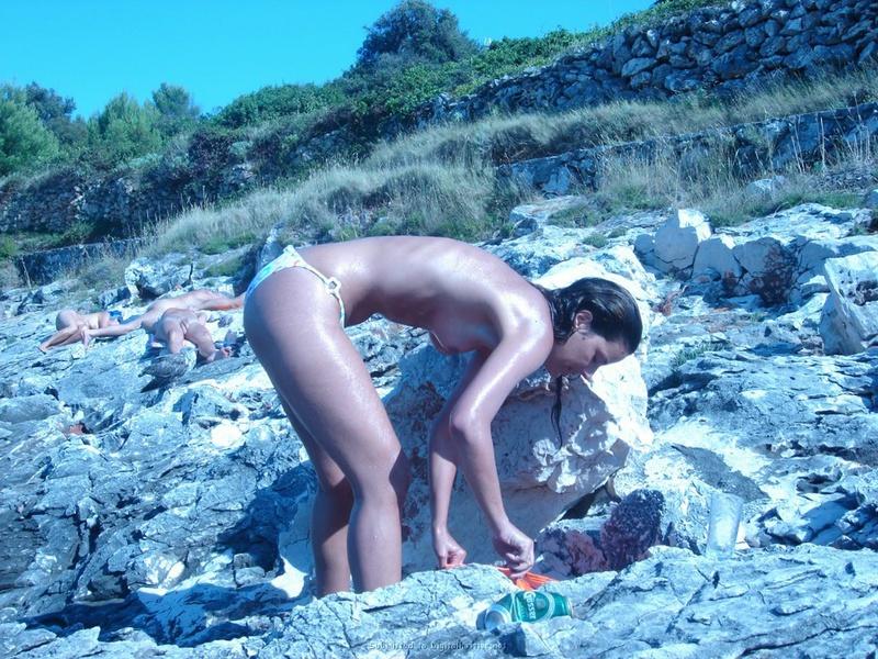 Стройная нудистка загорает на камнях