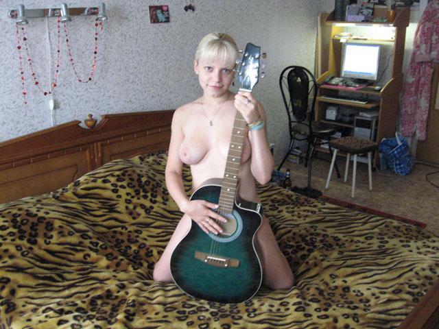 Блонда с огромным бюстом трогает гитару